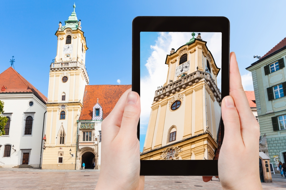 travel concept - tourist snapshot of Old Town Hall at Main Square in Bratislava on tablet pc